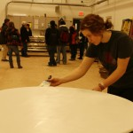 A student paints a table in the scene shop while journalism students interview theater department chair Ron Shields.
